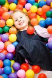 Smiling Child in colorful balls looking into camera. stock photo