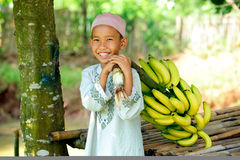 Child with Bananas. Happy Muslim boy holding bananas Stock Photo