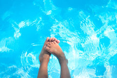 Child bare feet above blue water in swimming pool Royalty Free Stock Photography