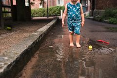 Child bare feet splashing water in a puddle Stock Image