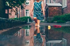 Child bare feet walking in a puddle of water royalty free stock photos