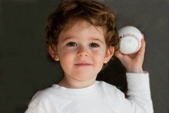 Child with baseball. A portrait of a cute little boy throwing a baseball, on a gray studio background.  This is the 4800000th image online Royalty Free Stock Images