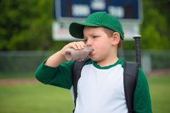 Child baseball player drinking chocolate milk. After game Stock Image