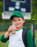 Child baseball player drinking chocolate milk. After game Royalty Free Stock Photography