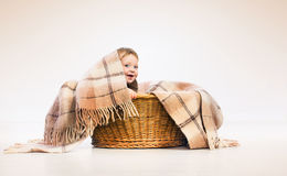 Child in basket with towel. Textile and bedding for kids. Cute boy baby in a laundry basket. Textile and bedding for kids. Little child on a pile of towels Stock Images