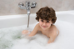 Child in the bath. Small child happy and smiling in the bath royalty free stock photography