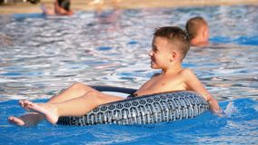 Child Bathes on an Inflatable Circle in the Pool with Blue Water. Slow Motion. Child Bathes on an Inflatable Circle in the Pool with Blue Water. Happy boy swims stock video footage
