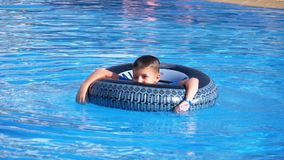 Child bathes on an inflatable circle in the pool with blue water. Slow motion. Child bathes on an inflatable circle in the pool with blue water. Happy boy swims stock footage