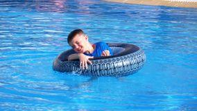 Child bathes on an inflatable circle in the pool with blue water. Slow motion. Child bathes on an inflatable circle in the pool with blue water. Happy boy swims stock video