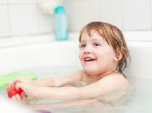 Child bathes with toys in bathtub Royalty Free Stock Photos
