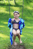 Child in bathing suit on swing Stock Image