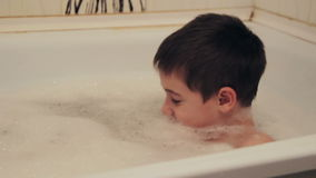 A child in the bathroom. The child takes a bath with  foam stock video footage