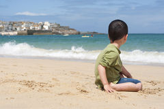 Child on beach in Cornwall. Child sitting on a beach looking at the sea in a Cornish seaside village and port of St. Ives in Cornwall, England, UK Stock Photos