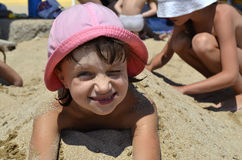Child on the beach. Covered with sand Stock Photography
