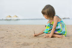 Child on the beach. The child draws a stick on the beach Royalty Free Stock Photography