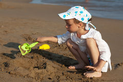 Child on the beach playing with sand. Royalty Free Stock Photography