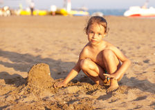 Child on the beach playing with sand. Stock Photos