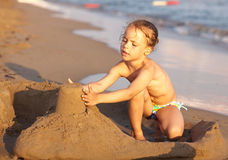 Child on the beach playing with sand. Royalty Free Stock Photo
