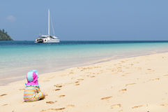 Child on a beach. Child sitting on a beach, sailboat in the background Royalty Free Stock Photography