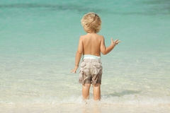 Child at the beach on a summer day. Child in the tropical caribbean blue water, during summer vacation. Photo taken in Nassau Bahamas Stock Image