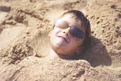 Child on the beach. Child with sunglasses on the beach Stock Photography