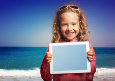 Child on the beach with tablet  pc Stock Photography