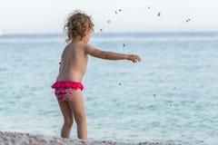 Child on the beach throws small stones into the sea stock photos