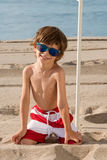 Child on the beach under umbrella with sunglasses on knees Stock Image