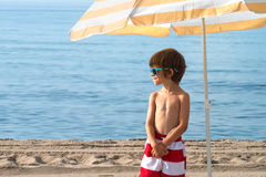 Child on the beach under umbrella with sunglasses looking to the Stock Images