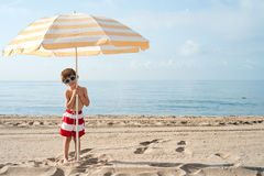 Child on the beach under umbrella with sunglasses Stock Image