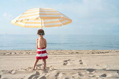 Child on the beach under umbrella with sunglasses Stock Photography