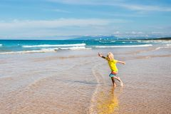 Child on tropical beach. Sea vacation with kids. Child on beautiful beach. Little boy running and jumping at sea shore. Ocean vacation with kid. Children play Royalty Free Stock Photos