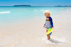 Child on tropical beach. Sea vacation with kids. Child on beautiful beach. Little boy running and jumping at sea shore. Ocean vacation with kid. Children play Stock Image