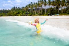 Child on tropical beach. Sea vacation with kids. Child on beautiful beach. Little boy with toy boat running and jumping at sea shore. Ocean vacation with kid Royalty Free Stock Photography