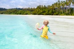 Child on tropical beach. Sea vacation with kids. Child on beautiful beach. Little boy with toy boat running and jumping at sea shore. Ocean vacation with kid Stock Photos