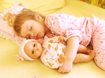 The child in the bed with a doll. The girl sleeps on a bed with a doll Stock Photo
