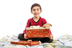 Child in bed opening present in Christmas eve Stock Images