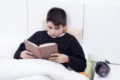 Child in bed reading Stock Photo