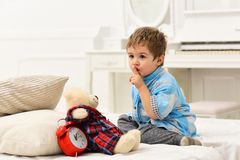 Child in bedroom with silence gesture. Boy with calm face puts favourite toy on bed, time to sleep. Kid put plush bear stock images