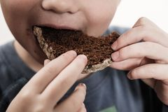 Child beggar eating cheap bread. Poor children and people donations Volunteers Concept. Child beggar eating cheap dirty bread. Poor children and people Royalty Free Stock Photo