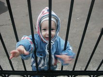 Child behind gate. A small child in winter clothes behind a closed black metal gate Royalty Free Stock Image