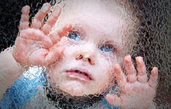Child behind the glass. Royalty Free Stock Photos