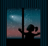 Child behind the window is watching the comet Stock Photo