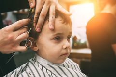 The child is being cut hairstyles. In the hairdressing salon stock photo