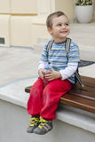 Child on bench with bottle of water Royalty Free Stock Images