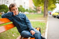 Child on a bench in a park. Cute kid sitting on a bench in a park Royalty Free Stock Photography