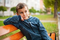 Child on a bench in a park. Cute kid sitting on a bench in a park Stock Photos