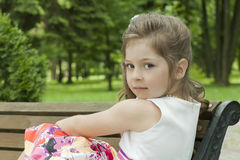 Child on a bench in park Stock Photo