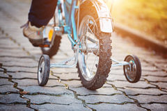 Child on a bicycle on asphalt road in sunny day. Back view. Stock Photo