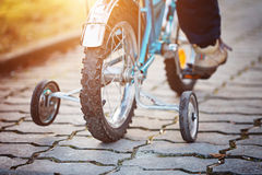 Child on a bicycle  asphalt road in sunny day. Back view. Stock Image
